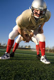 American football running back passing ball through legs to quarterback during competitive game, front view (surface level) Royalty Free Stock Photo