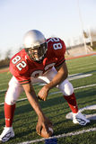 American football running back, in red football strip, crouching with ball in scrimmage line during competitive game, front view ( Stock Photos