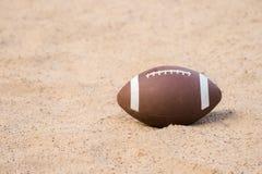 American football in the sand on the beach stock photos