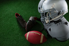 American football shoulder pads, head gear, football and cleats over artificial turf stock photos