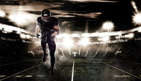 American football sportsman player on stadium in action. Sports banner and wallpaper with copyspace. American Football player on stadium with smoke and lights royalty free stock image