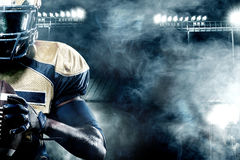 American football sportsman player on stadium with lights on background with copy space. American Football player on stadium with smoke and lights with copy stock image