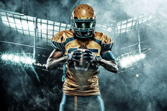 American football sportsman player on stadium with lights on background. American Football player on stadium with smoke and lights stock images