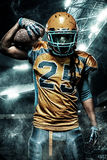 American football sportsman player on stadium with lights on background. American Football player on stadium with smoke and lights Stock Photos
