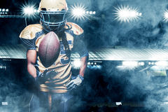 American football sportsman player on stadium running in action. American Football player on stadium with smoke and lights Royalty Free Stock Photography