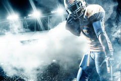 American football sportsman player on stadium running in action. American Football player on stadium with smoke and lights Royalty Free Stock Photo