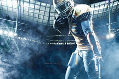 American football sportsman player on stadium running in action. American Football player on stadium with smoke and lights Stock Images