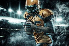 American football sportsman player on stadium running in action. American Football player on stadium with smoke and lights stock photos