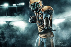 American football sportsman player on stadium running in action. American Football player on stadium with smoke and lights Royalty Free Stock Image