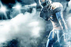 American football sportsman player on stadium running in action. American Football player on stadium with smoke and lights Royalty Free Stock Photos