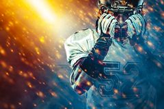 American football sportsman player on stadium running in action. Sport wallpaper with copyspace. Team sports.