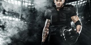 American football sportsman player on stadium. Sports banner and wallpaper with copyspace. American Football player on stadium with smoke and lights royalty free stock images