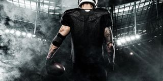 American football sportsman player on stadium. Sports banner and wallpaper with copyspace. American Football player on stadium with smoke and lights stock image