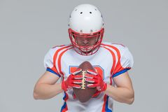 American football sportsman player wearing helmet holding rugby ball isolated on grey background.  stock image