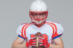 American football sportsman player wearing helmet holding rugby ball isolated on grey background.  royalty free stock images