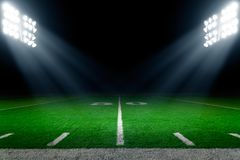 American football stadium background. With stadium lights, 50 yards line in the middle Royalty Free Stock Image