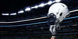 American Football Stadium. A football player raises his helmet during a football game in a large indoor football stadium Stock Image