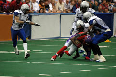 American Football tackle. A football player holding football and being taken down by three players (motion blur stock photography