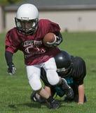 American Football tackle in his wake. October 10, 2009 American Football (Youth 4-5th Grade) Oregon's Hillsboro's Glencoe High School Crimson Tide youth V Stock Photo