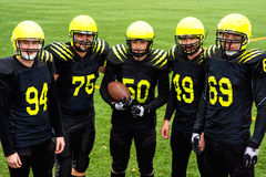 American football team. In sportswear with the ball standing together on the sports ground Stock Image