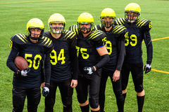 American football team. In sportswear with the ball standing together on the sports ground Royalty Free Stock Photography