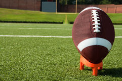 American Football on Tee. Closeup of American football on tee with goal post in background Royalty Free Stock Photos