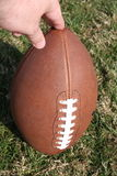 American football upright. Holding an American football upright in natural grass Stock Photography