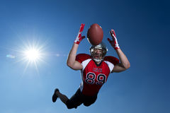 American Football Wide Receiver dives to make the catch Stock Photo