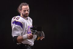 Footballer with smartfone on gimbal. American footballer online in social networks using a mobile phone on the stabilizer from studio royalty free stock photos