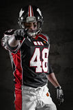 American footballer pointing at you. On dark background Stock Photo