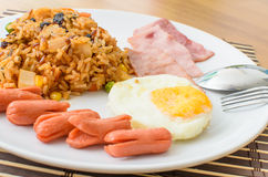 American fried rice with pork sausage, bacon and fried egg Stock Images