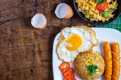.American fried rice served with fried eggs and sausages on the table stock photography