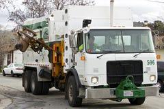 American garbage truck picks up the trash. San Jose, California, United States - January 22, 2016. White American garbage truck stopped on the road between the stock photo