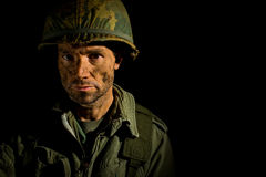 American GI Portrait - PTSD. Close up of an American G.I. from the Vietnam War period, with face covered in dirt and mud Royalty Free Stock Photography