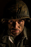 American GI Portrait - PTSD. Close up of an American G.I. from the Vietnam War period, with face covered in dirt and mud Royalty Free Stock Images