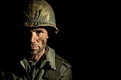 American GI Portrait - PTSD. Close up of an American G.I. from the Vietnam War period, with face covered in dirt and mud Stock Image