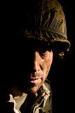 American GI Portrait - PTSD. Close up of an American G.I. from the Vietnam War period, with half his face in shadow Stock Photography