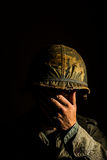 American GI Portrait - PTSD. Close up of an American G.I. from the Vietnam War period, with his hand covering his face Royalty Free Stock Photo