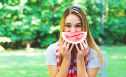 American girl eating watermelon. American girl with red striped scarf eating watermelon outside royalty free stock image