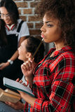 American girl holding notebook in thoughtful pose while her friends talking. African american girl holding notebook in thoughtful pose while her friends talking Royalty Free Stock Image