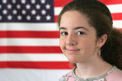American Girl Smiling. A teenaged girl smiling in front of an American flag stock images