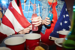 American Girls at Students Party. Mid-section portrait of two teenage girls drinking cocktails at late night party, wrapped in American banner Royalty Free Stock Photos