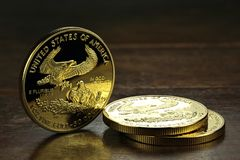 American gold eagle. 1 ounce American gold eagle bullion coins on wooden background stock image