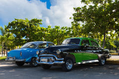 American green black and a blue vintage car parked under blue sky in Varadero Cuba Stock Photos