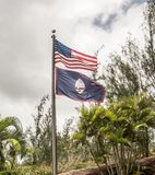 American and Guam Flags with Palm Trees in the Background stock photography