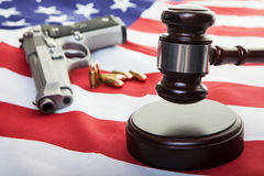 American Gun Law. A gavel on an american flag with a gun and bullets in the background, focus on the gavel Stock Image