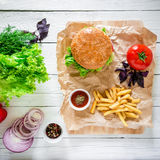 American hamburger with beef, french fries and vegetables on wood table. Top view. Flat lay. Royalty Free Stock Images
