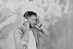 American handsome bearded guy with headphones. European guy have fun time. Cheerful teenage dj listening songs via. Earphones. Musical lifestyle. Blue eyed royalty free stock photography
