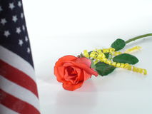 An American Heart Waits. Red Rose with Yellow Ribbon and American Flag Stock Photography