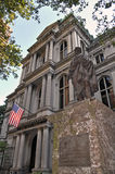 American Historic Building with Bronze Statue. City Hall historic building with American flag hanging over entrance way. Bronze statue on top of a marble stand Stock Images